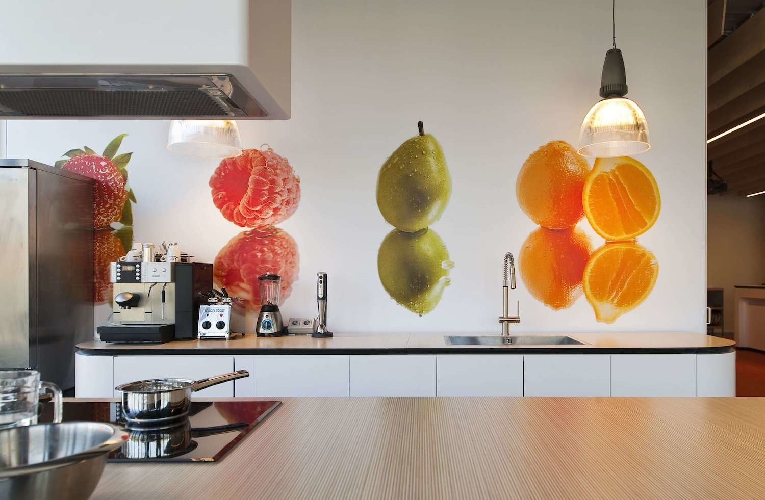Large sliding doors with fruit prints can close off or add the reception area to the kitchen and portray the fresh and open identity of the company.